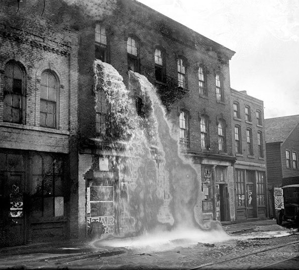 Illegal alcohol being poured out during Prohibition, Detroit, 1929