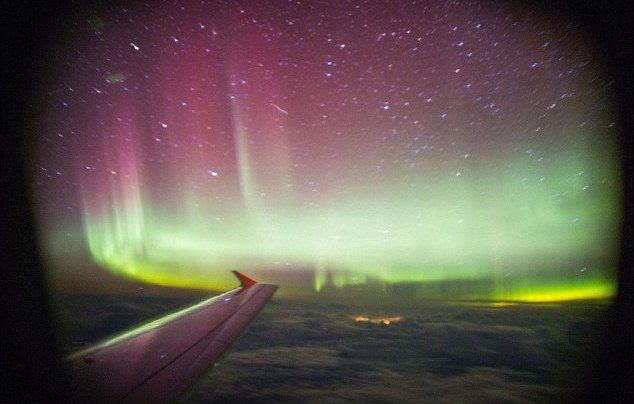 A traveller on a flight over the UK snaps a gorgeous photo of the Aurora Borealis out of a plane window.