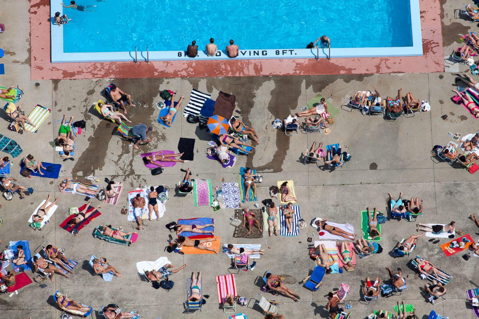 People tanning poolside in Cambridge, Massachusetts