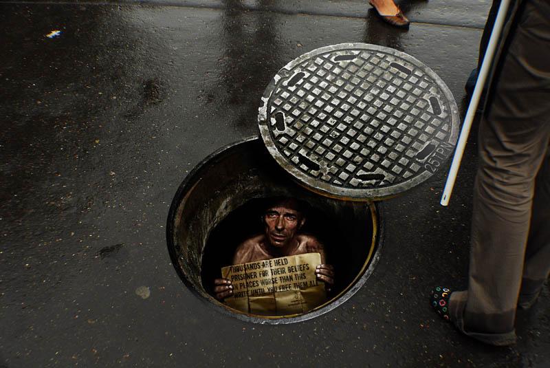 sidewalk-sticker-looks-like-a-person-is-inside-a-manhole