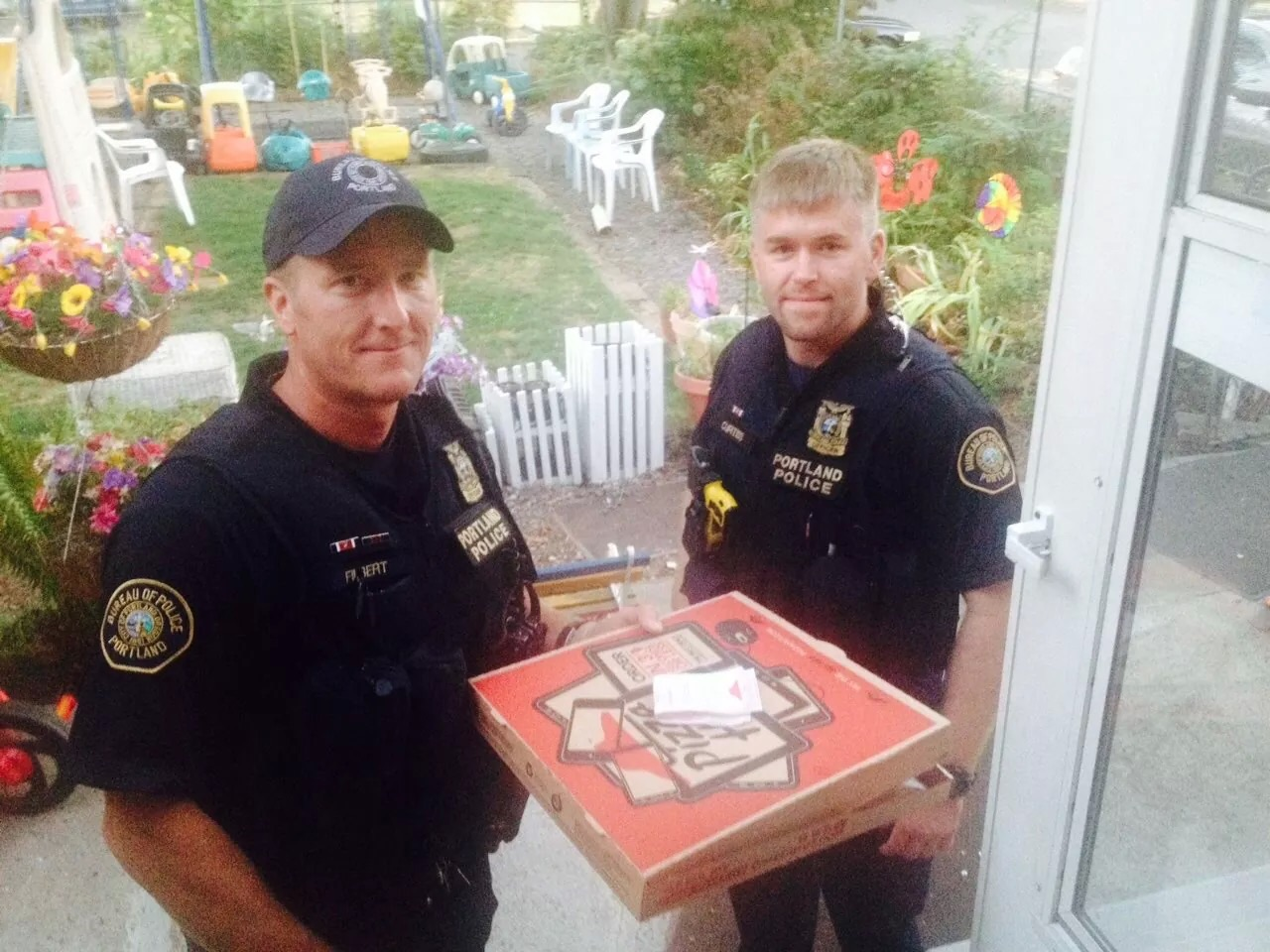 Police officers completing the pizza delivery for the delivery man who was involved in an accident